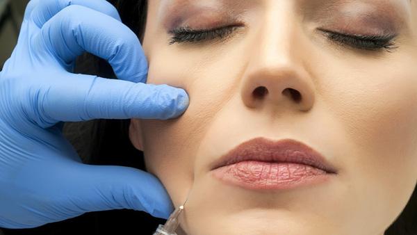 Инъекция ботокса в мышцу, опускающую уголки рта